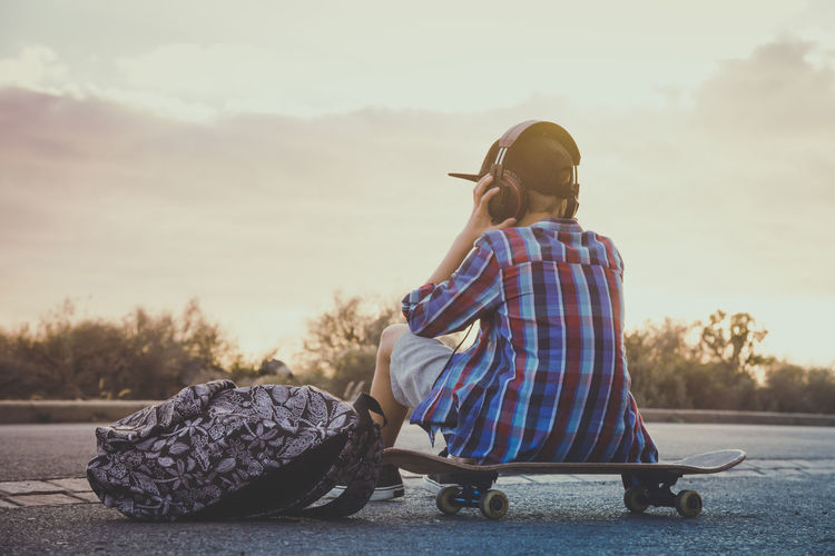 Rear View Of Boy Listening Music With Headphones While Sitting On Skateboard