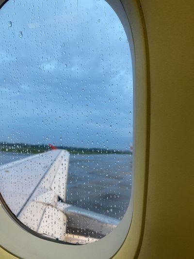 Airplane seen through wet window in rainy season