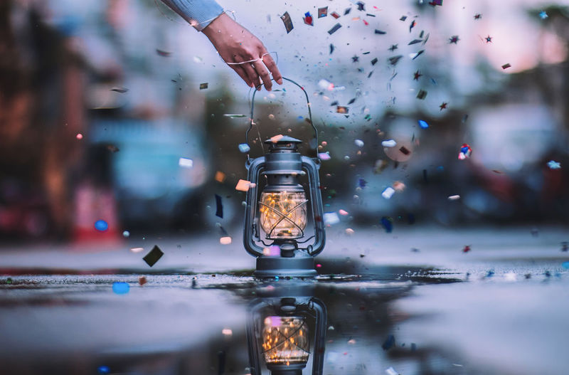 Cropped Image Of Hand Picking Up Illuminated Lantern With String Lights By Confetti On Street