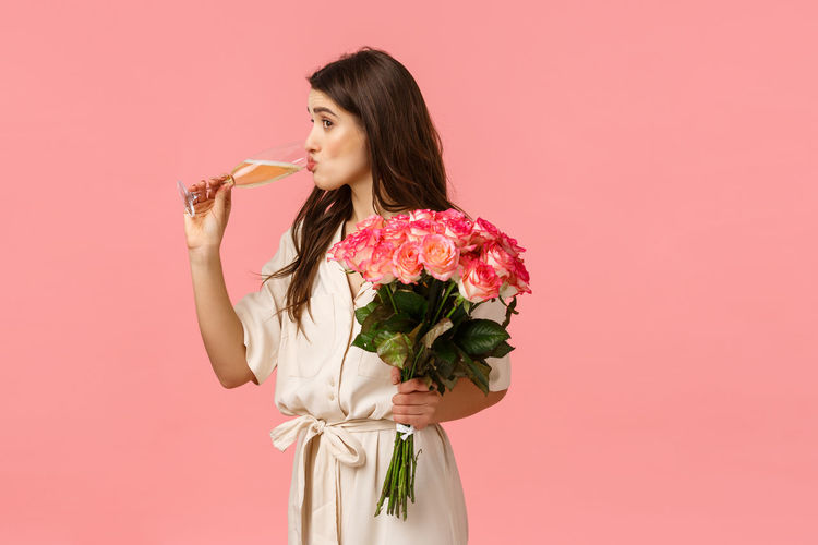 Woman holding pink rose against white background