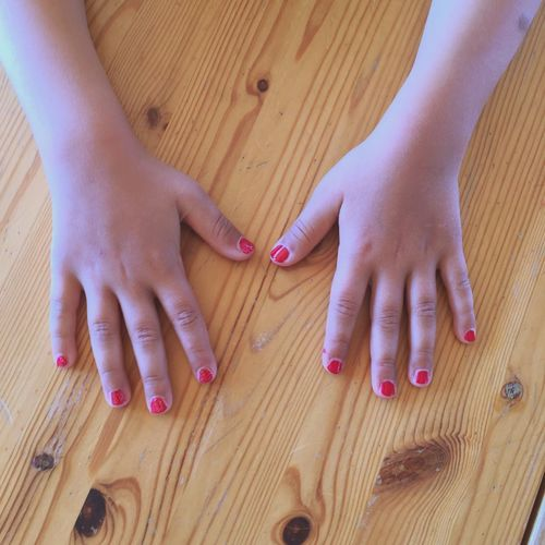 Cropped hands of woman with pink nail polish on wooden table