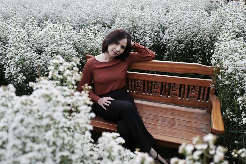 Portrait of woman sitting on bench amidst flowering plant