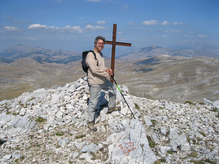 Full length portrait of man standing by cross on rock against sky