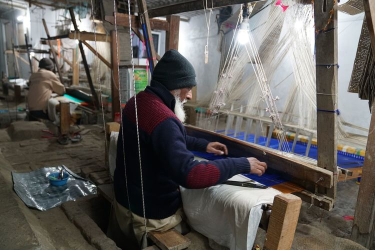 Adult Casual Clothing Clothing Concentration Culture Factory Full Length Handmade Holding Indiansilk Indoors  Industry Men Occupation One Person Real People Side View Sitting Technology Textile Varanasi Working Young Adult