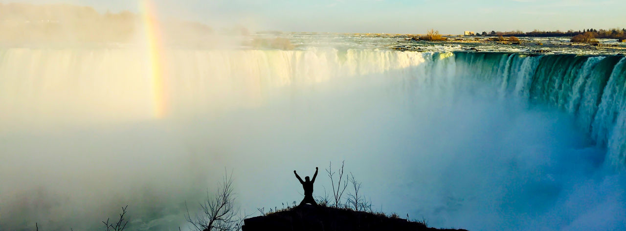 Man With Arms Raised Standing Against Niagara Falls