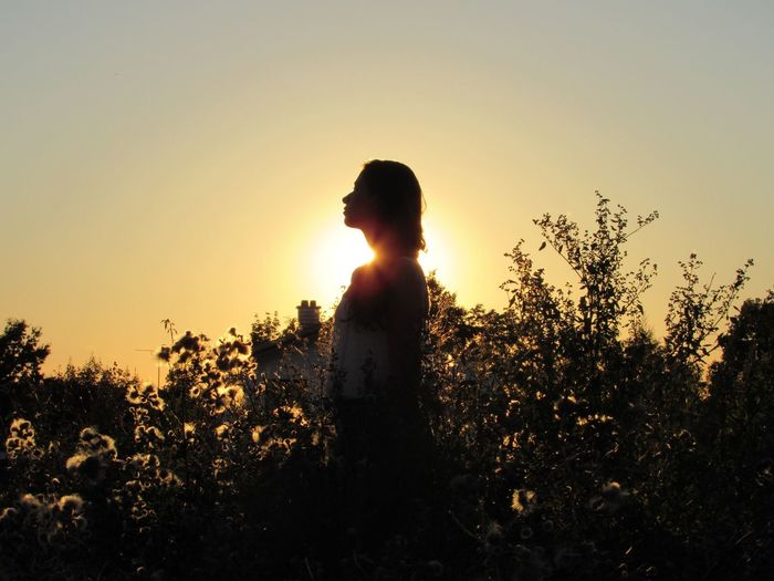 Silhouette Of Woman Standing On Field At Sunset