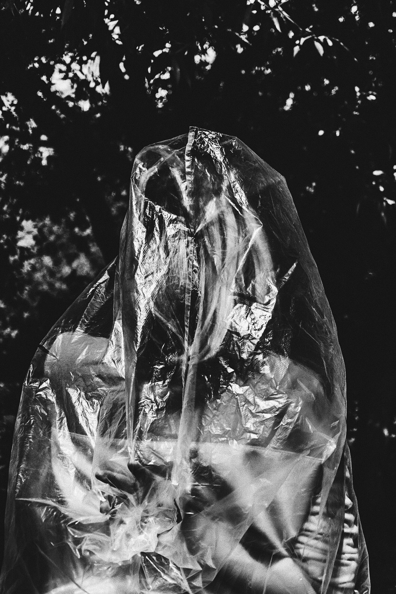 Young woman covered in plastic standing against trees
