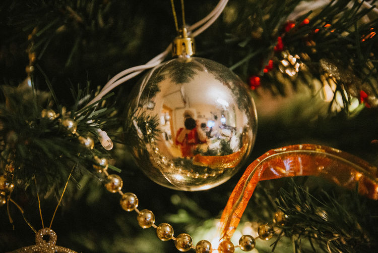 Close-up of christmas decoration hanging on tree with reflection of woman