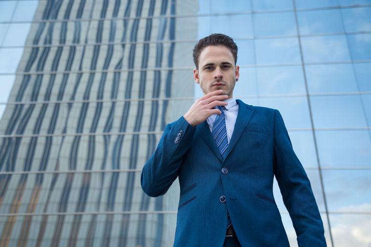 Low Angle Portrait Of Businessman Standing Against Office Building