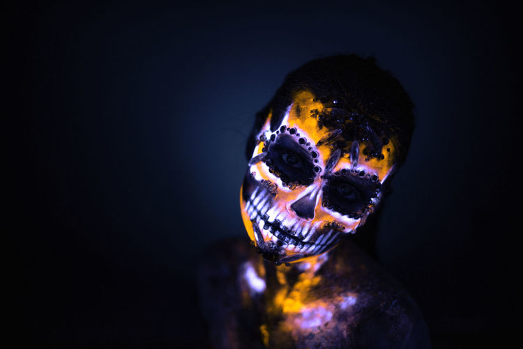 Close-up portrait of woman wearing illuminated spooky mask against black background