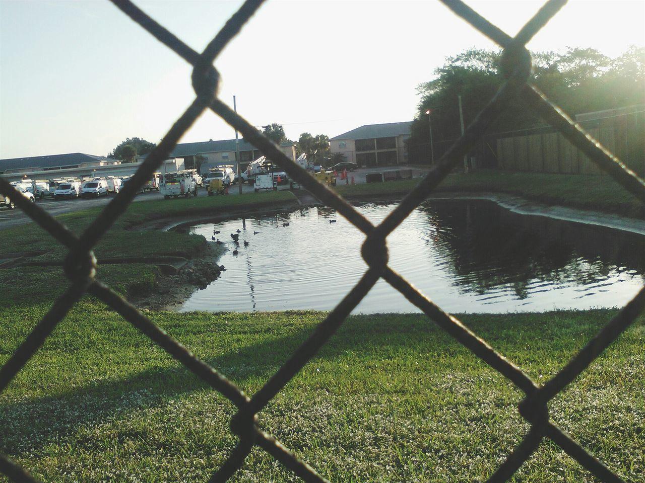 Pond Against Sky Seen Through Chainlink Fence