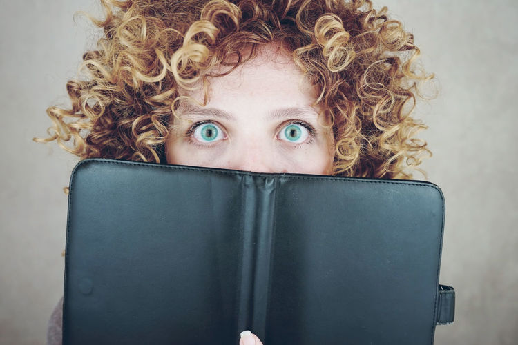 Close-up portrait of shocked young woman covering mouth with book against gray background