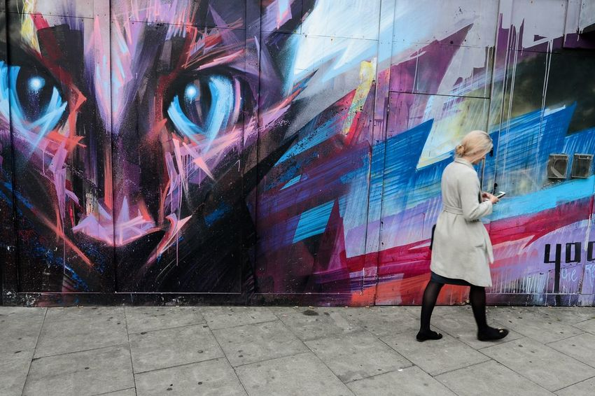 Cat Call - A young lady fiddling with her phone as she passes by a wall with street art. The cat's eyes watching her while she tries to attend a phone call. City Life Debarshi Mukherjee Photography London Moments Postcode Postcards Street Art/Graffiti Travel Day Debarshimukherjee Graffiti Multi Colored Outdoors People Real People Street Art Street Color Street Photography Streetphotography EyeEmNewHere An Eye For Travel Colour Your Horizn Stories From The City Visual Creativity #FREIHEITBERLIN