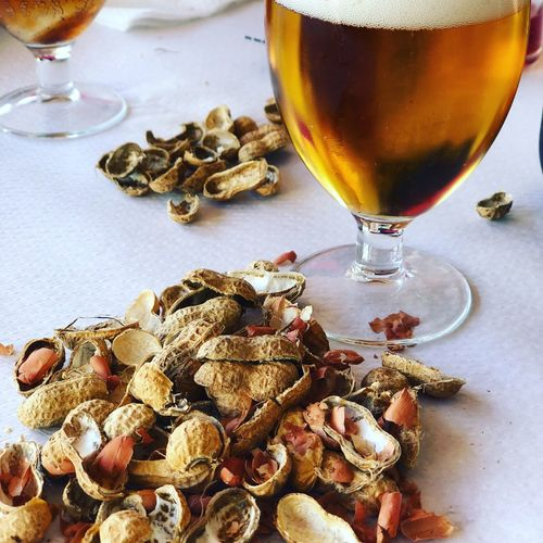 Close-up of beer with peanuts on table