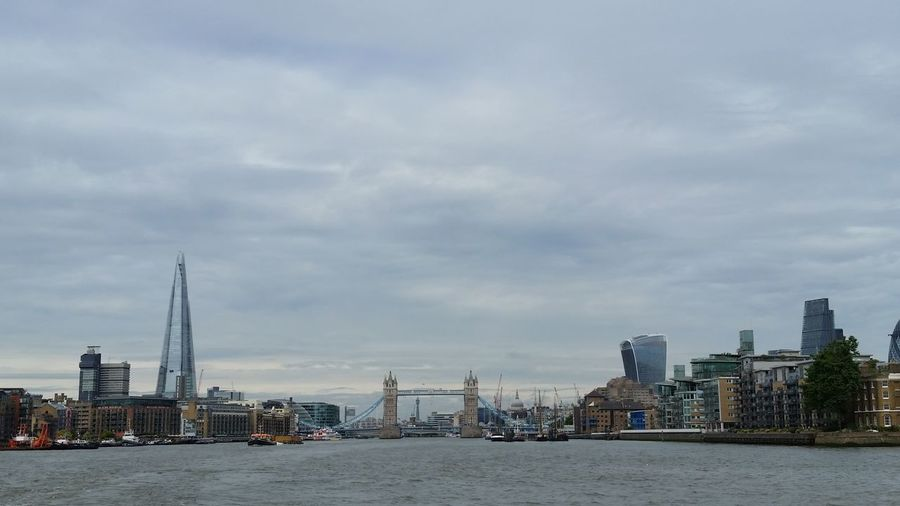 Thames river amidst buildings against cloudy sky