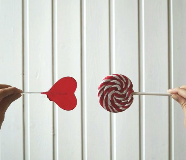 Cropped woman hands holding candies against white wall