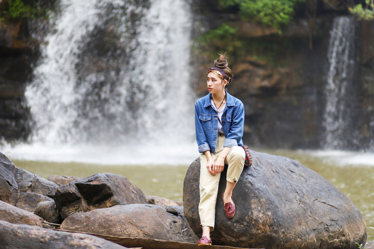 Full length of woman sitting on rock against waterfall