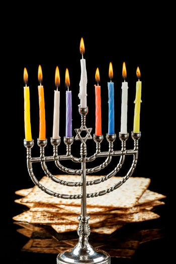Menorah with lighted candles for Hanukkah on a black in the background. Anniversary Birthday Birthday Cake Birthday Candles Black Background Burning Cake Candle Celebration Chanuka Chanukah Close-up Culture Dark Event Fire Fire - Natural Phenomenon Flame Food And Drink Hanukkah Heat - Temperature Illuminated Indoors  Matchstick Matzo Matzoth Menorah Multi Colored No People Studio Shot Temptation