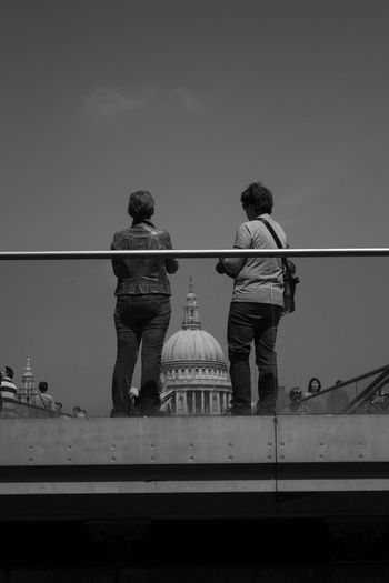 Rear view of people on bridge looking at st paul cathedral against dome
