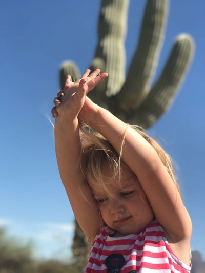 Close-up of girl with arms raised against cactus