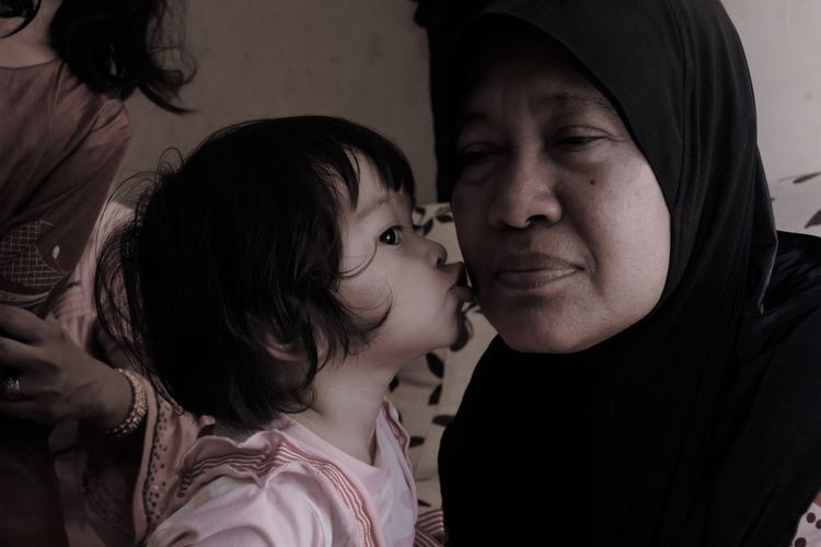 Close-up of baby girl kissing grandmother at home