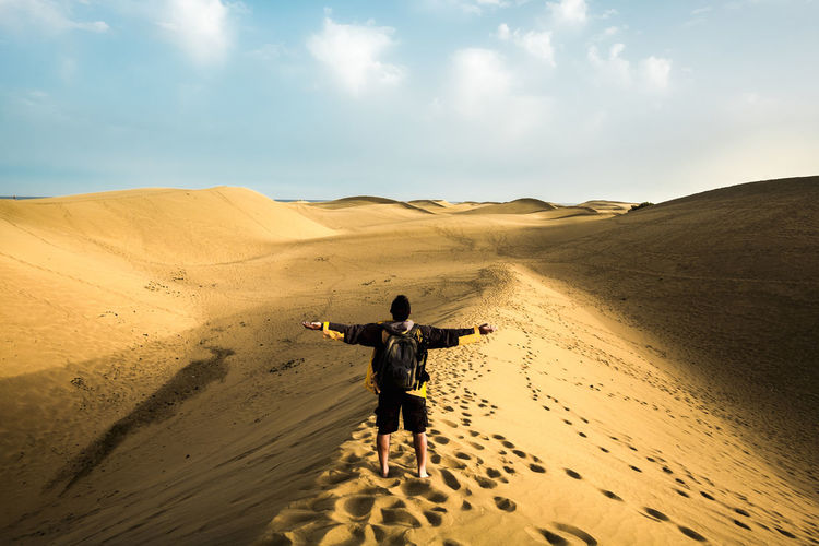 Rear view of man with arms outstretched while standing at desert