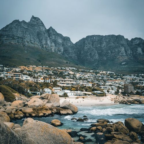 Scenic view of sea by buildings against mountains