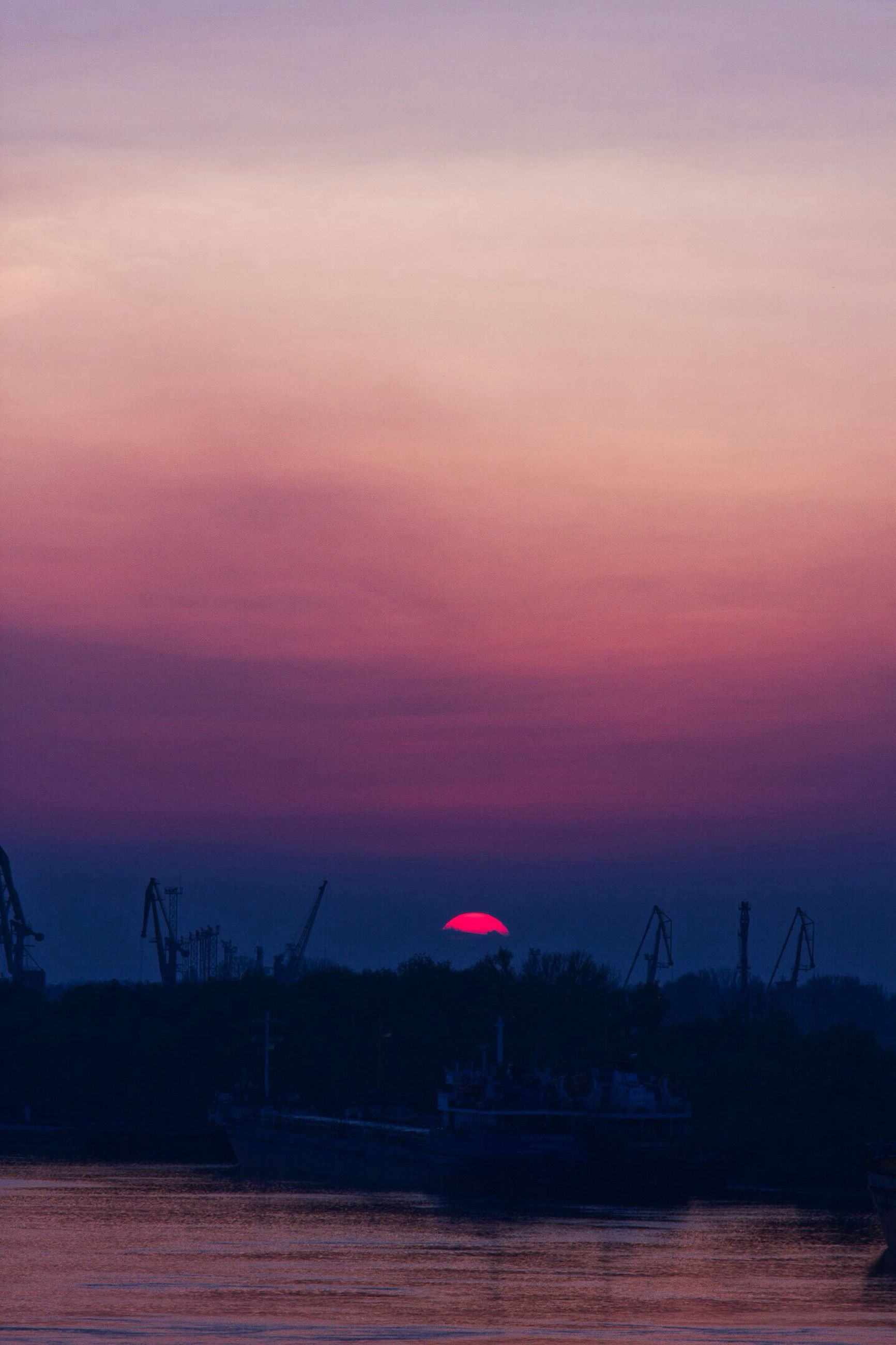sunset, silhouette, crane - construction machinery, cloud, scenics, tranquil scene, water, sky, tranquility, sea, calm, ocean, development, outline, orange color, crane, waterfront, beauty in nature, dramatic sky, nature, majestic, harbor, romantic sky, sun, outdoors, cloud - sky, no people, moody sky