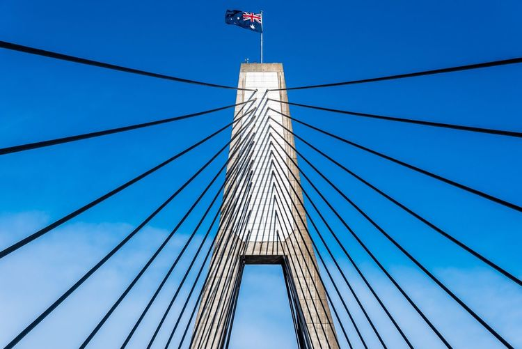 Low angle view of suspension bridge with australian flag against sky