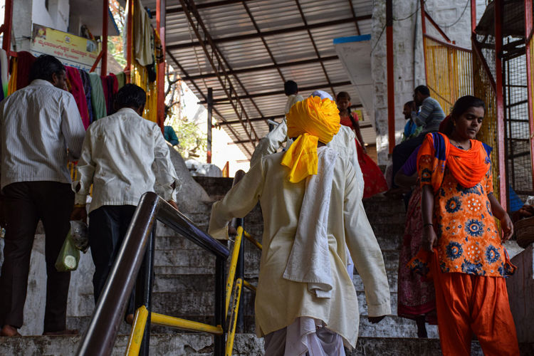 Rear view of people standing on temple