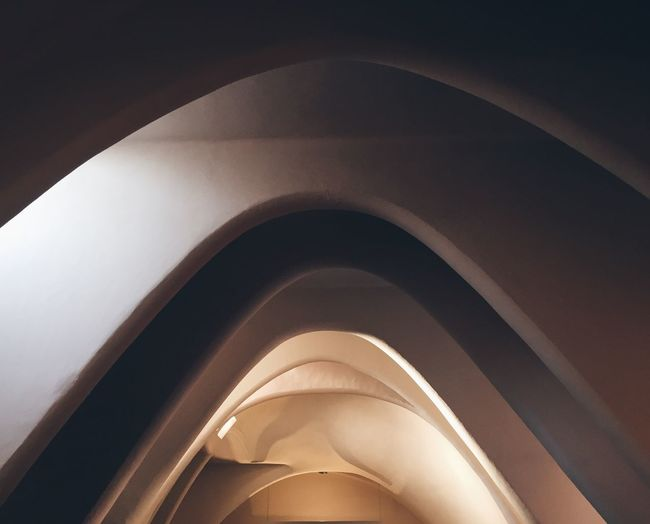 Low Angle View Of Illuminated Curve Shape Ceiling In Building
