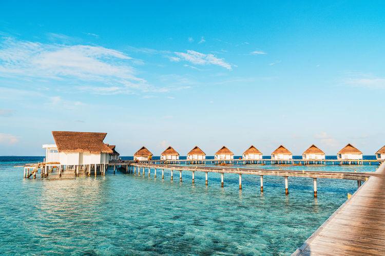 Stilt houses by swimming pool against sky