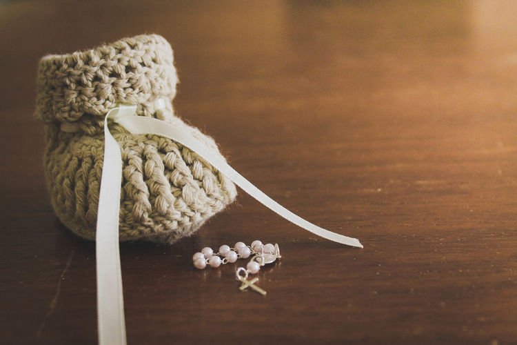Close-Up Of Knitted Baby Bootie With Rosary Beads On Table