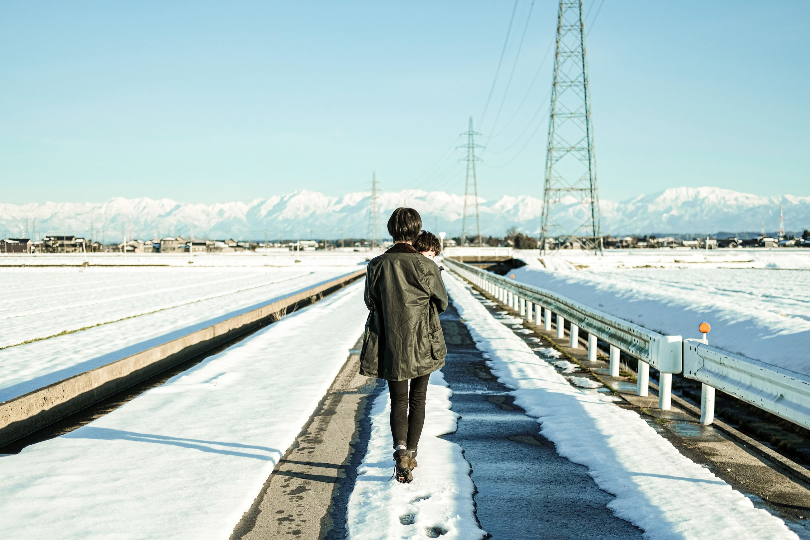 rear view, winter, cold temperature, snow, transportation, sky, nature, real people, one person, day, electricity, sunlight, clothing, full length, connection, electricity pylon, rail transportation, cable, track, outdoors, warm clothing, power supply