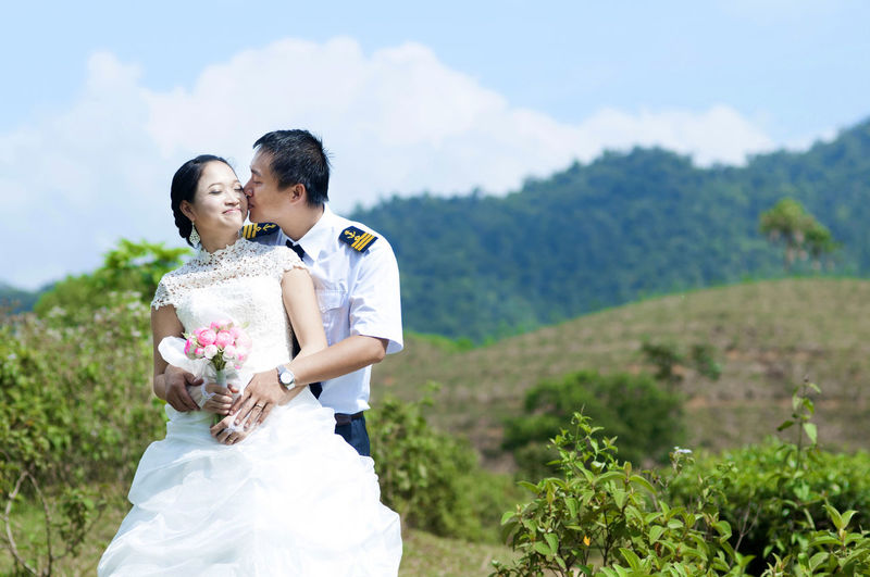 Happy bridegroom kissing bride on cheek against mountains