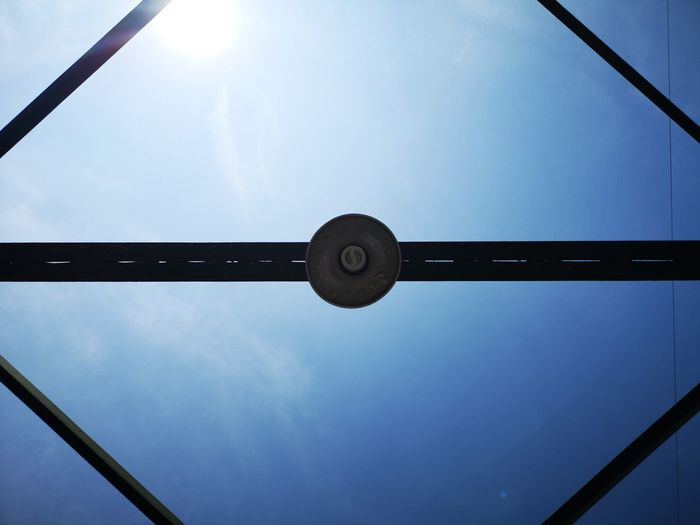 Low angle view of electric lamp against sky