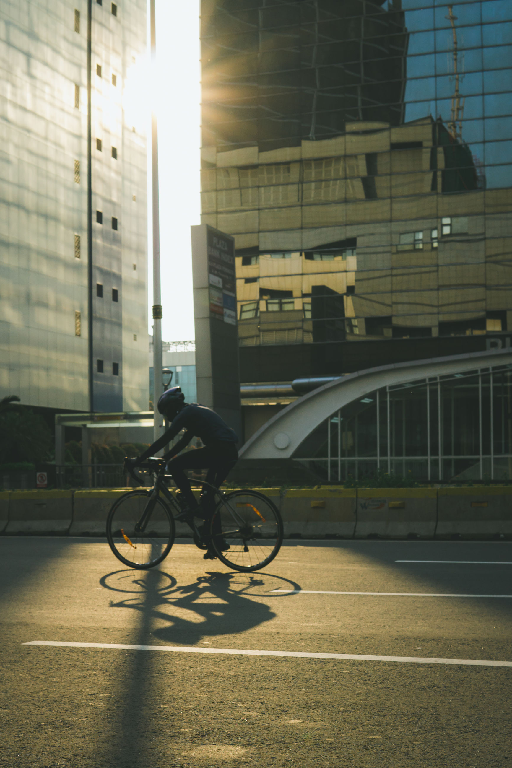 building exterior, built structure, architecture, bicycle, transportation, city, mode of transportation, land vehicle, sunlight, building, street, day, nature, outdoors, shadow, one person, office building exterior, real people, riding