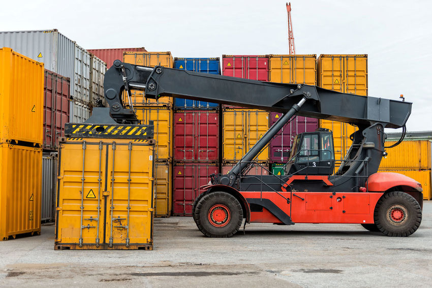 Mobile stacker handler in action at a container terminal. Harbor Architecture Building Exterior Built Structure Cargo Container Day Distribution Warehouse Export Forklift Freight Transportation Import Industry Logistic No People Outdoors Red Sky Stack Terminal Transfer Transportation