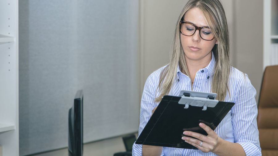 Close up of beautiful young woman writing notes at workplace Business Busy Company Female Power Glasses Horizontal Leader Woman Working Writing Beauty Business Finance And Industry Businesswoman Caucasian Chief Executive  Female Headquarters Job Notebook One Person Portrait Professional Real People Sucess