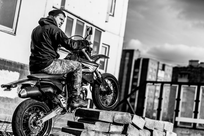 Motorcycle Biker Mode Of Transport Transportation Riding Land Vehicle Motorized Vehicle Riding Built Structure Men One Person City Motorcycle Racing One Man Only Cycling Outdoors Building Exterior Sky City Life Alternative Lifestyle Only Men