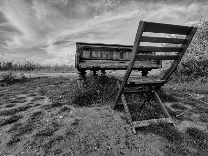 Abandoned bench on field against sky