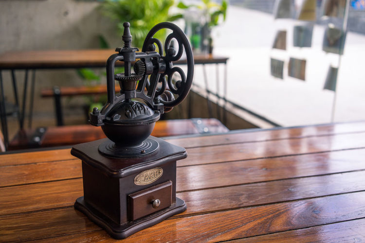 Close-up of coffee grinder on wooden table