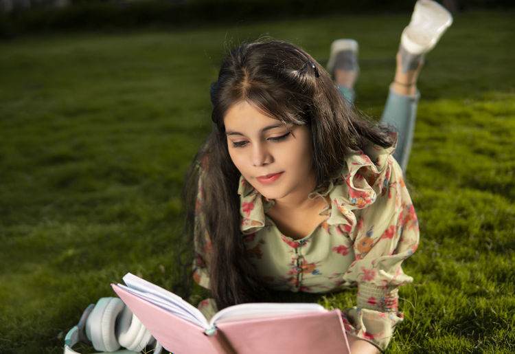 Beautiful young woman reading book on field