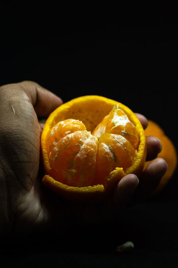 Close-up of hand holding orange fruit against black background