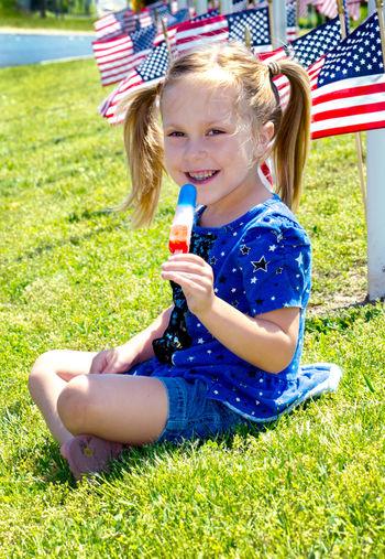 Happy girl sitting on grass