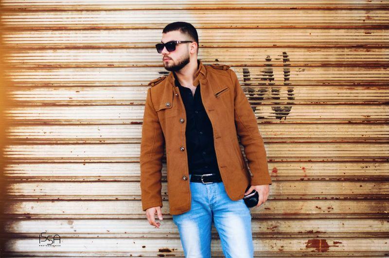 Handsome man standing against shutter