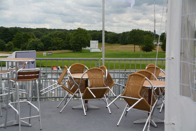 Empty Chairs And Table Against Golf Course