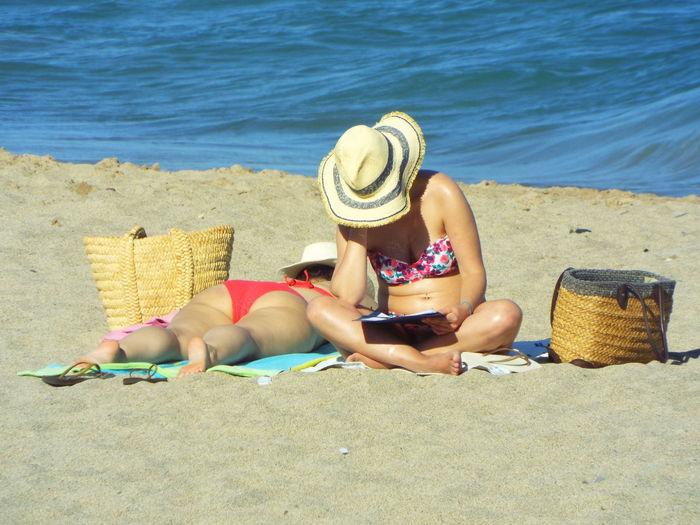Women Sunbathing At Beach Against Sea