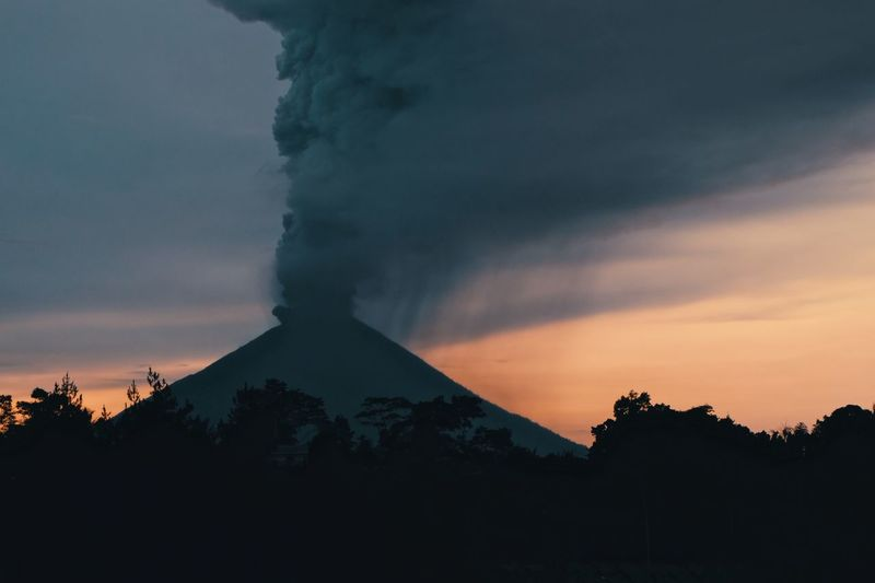 Smoke Erupting From Mountains Against Sky During Sunset