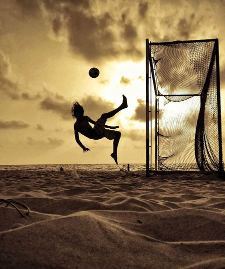 Side view of silhouette man jumping and kicking ball at beach